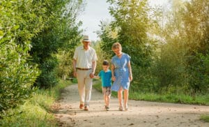 happy grandparents walking nature trail with grandson