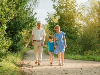 Front view of grandparents and grandchild walking on a nature path