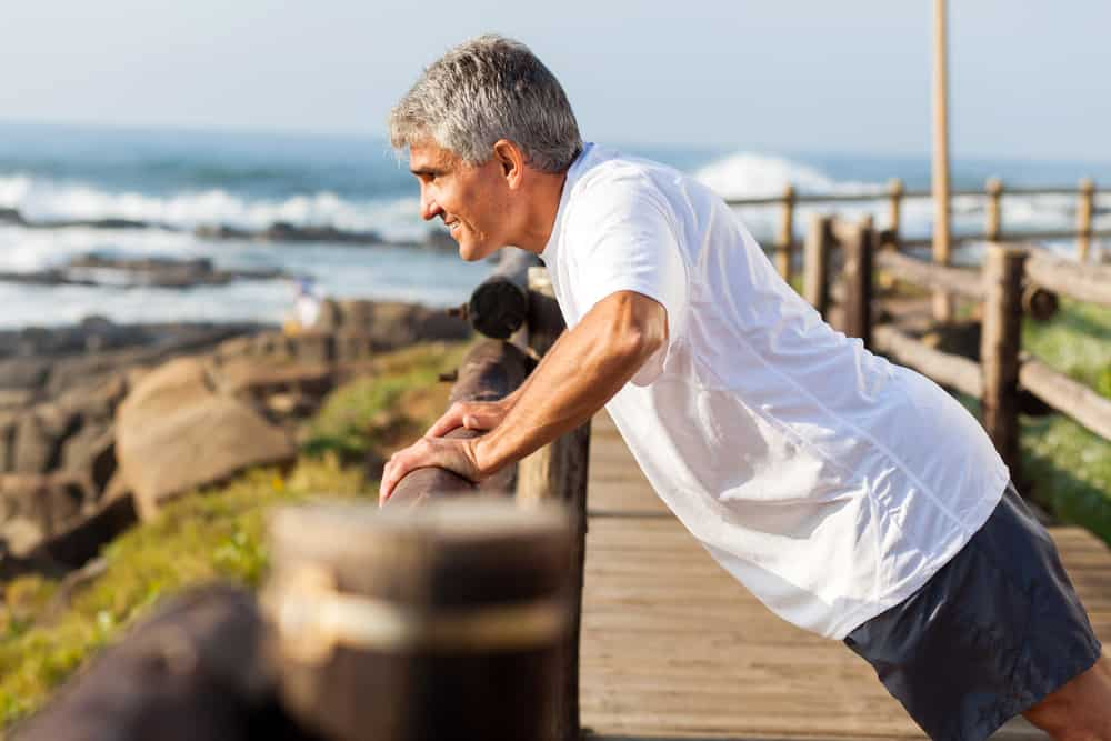 mature man looking over pier