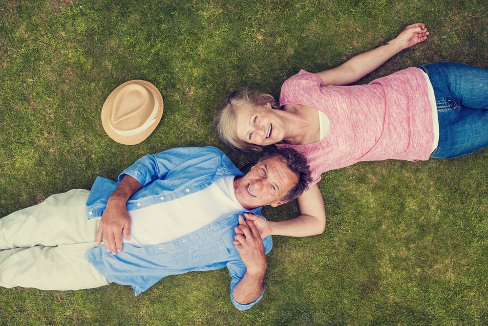 couple laying in grass holding hands mature