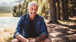 happy mature man sits by lake