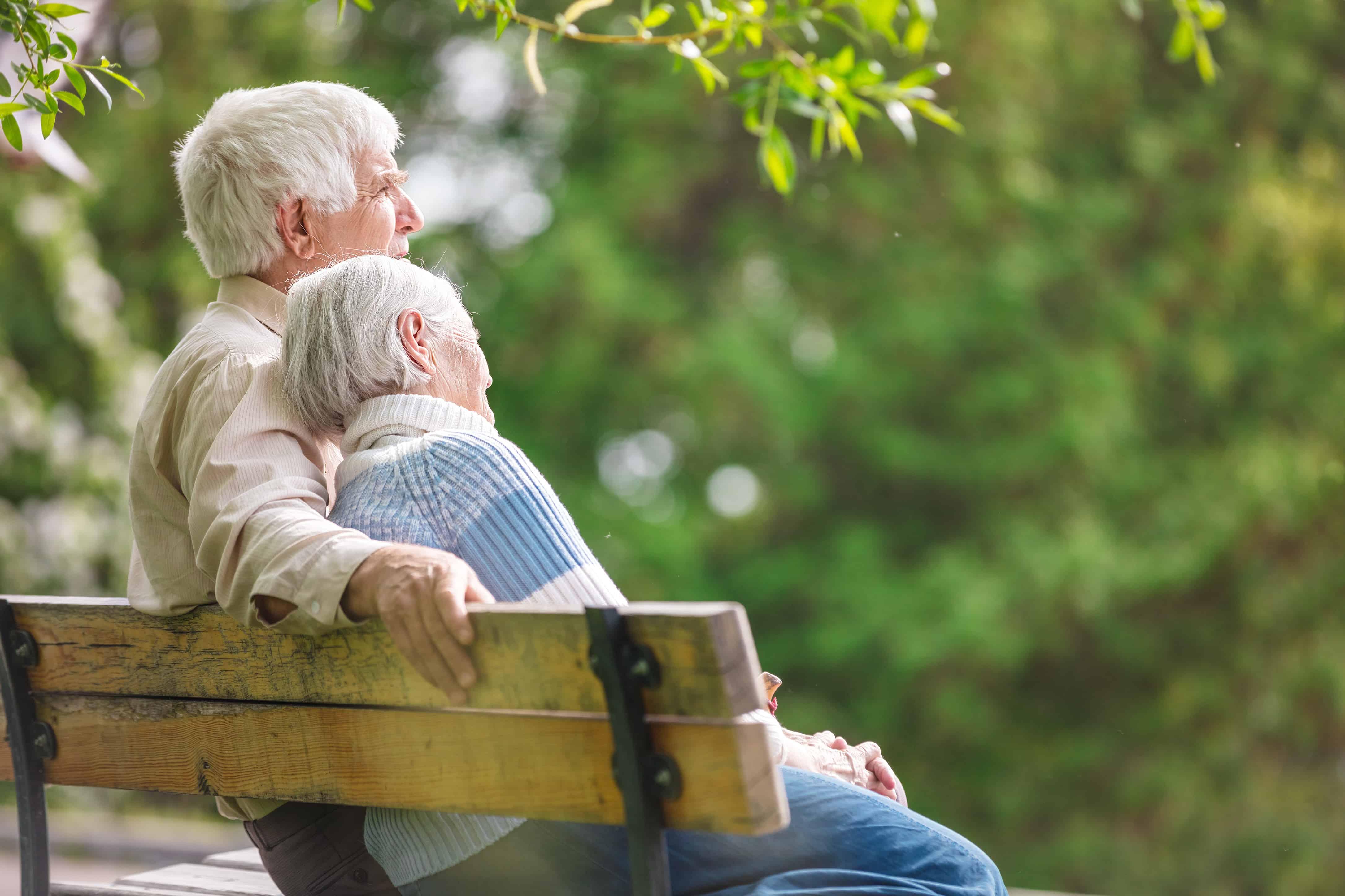 couple sitting on park bench elderly