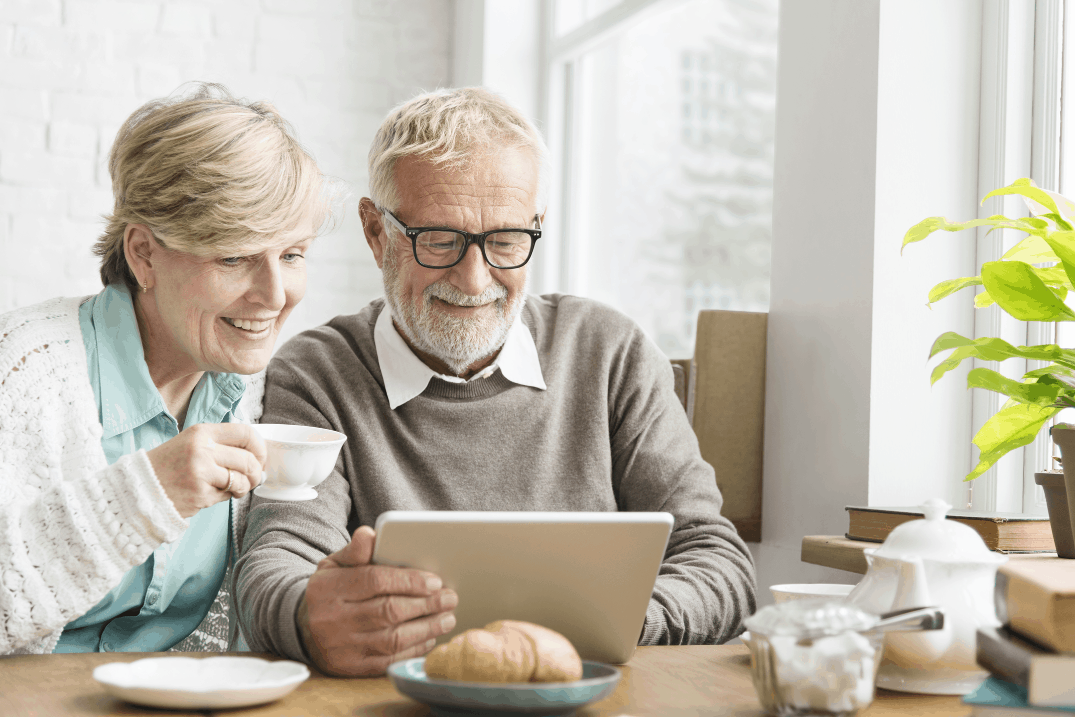 couple looking at tablet over breakfast