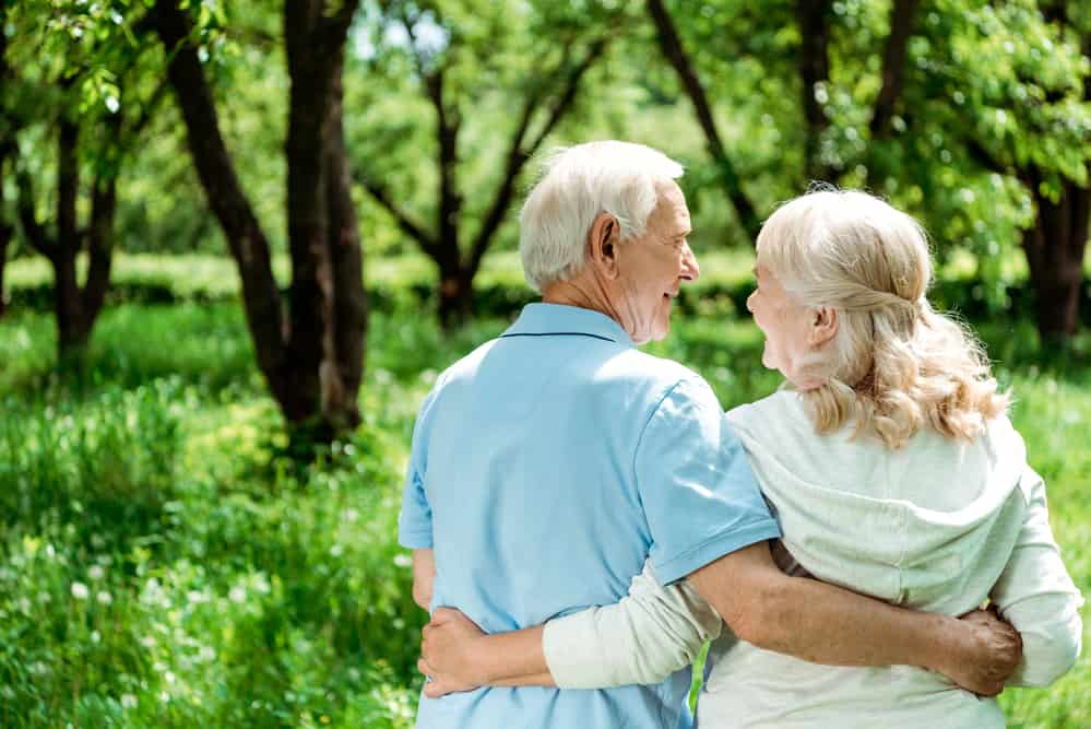 older couple walking through forest