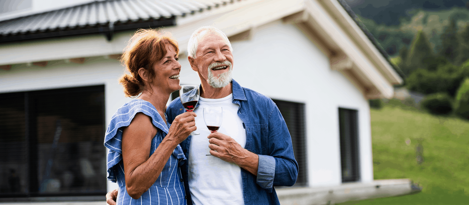 happy couple with wine in front of house looking into the distance